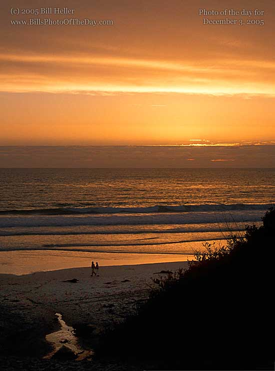 Couple walking on the beach at sunset in Carmel, California