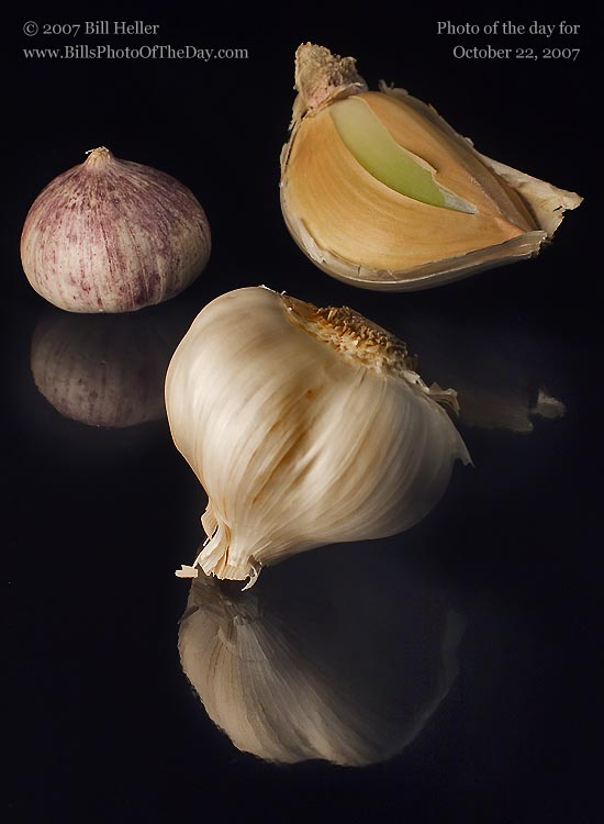 Three types of garlic on a shiny black surface